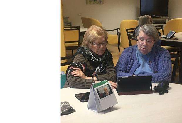 Deux résidentes qui manipulent une tablette Ardoiz.