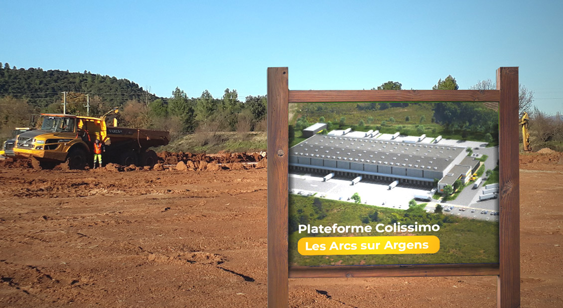 Photo of The project site after clearing, with a sign giving an idea of the scale of the site after construction.