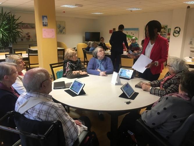 Sept seniors de la résidence « Le Square des âges », assis autour d'une table ronde, en train d'écouter la formatrice Ardoiz.