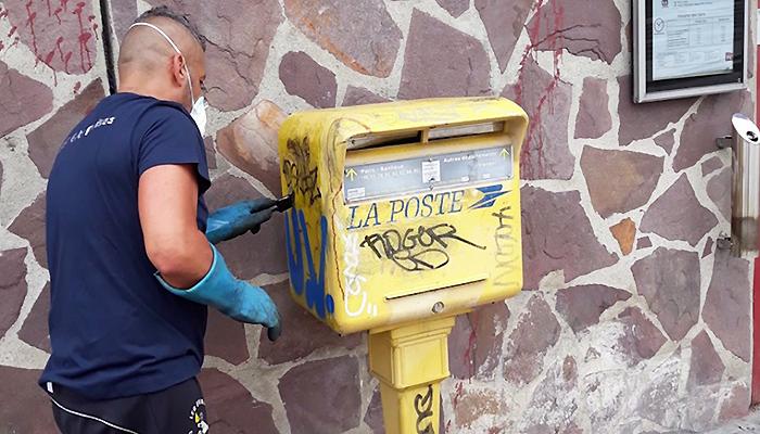 Un salarié de l'Association des Paralysés de France nettoyant une boîte aux lettres de rue.