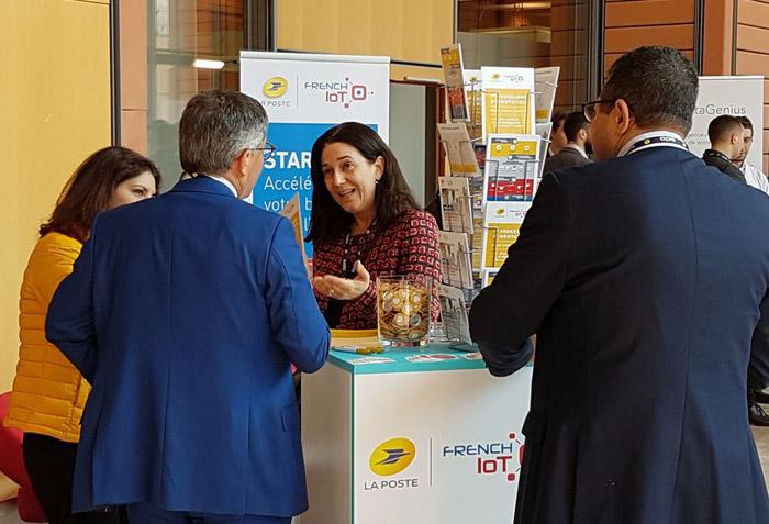 Photo du stand de La Poste au Sido 2019, avec Vanessa Chocteau expliquant à un visiteur le programme d'accélération French IoT