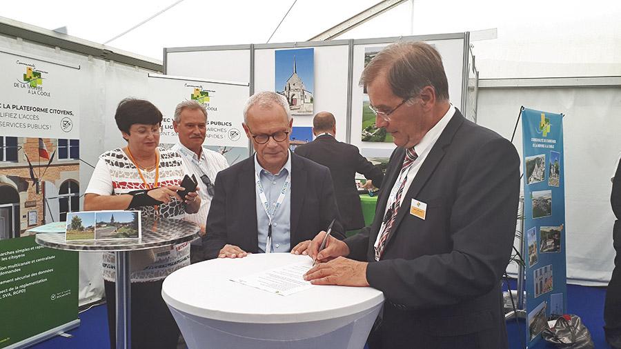 Photo de la signature de la convention entre la communauté de communes de la Moivre à la Coole et Docaposte, lors du Carrefour des élus à la foire de Châlons-en-Champagne.
