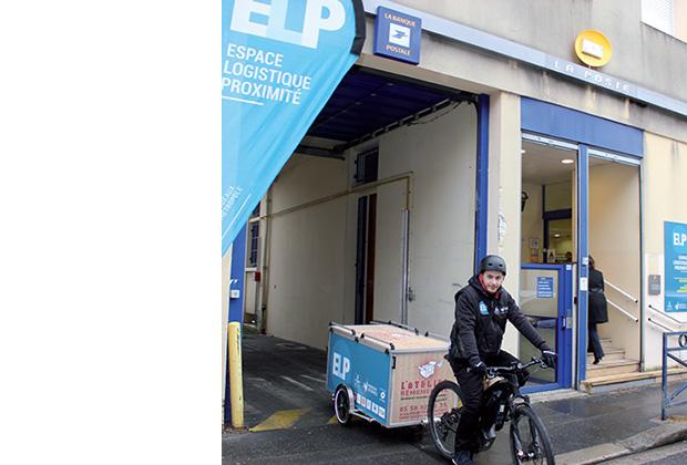 Photo de l'espace logistique de proximité de Bordeaux, avec un livreur qui en sort, conduisant un vélo avec remorque