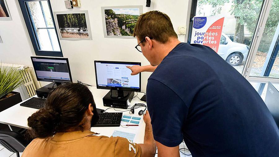 Un médiateur social aidant un client dans son utilisation d'un site internet de services publics.