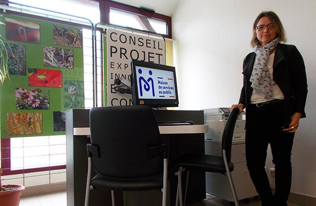 Photo avec un îlot numérique (maison de services au public affiché sur l'écran de l'ordinateur) et Sarah Lambérioux, gérante de l'agence.
