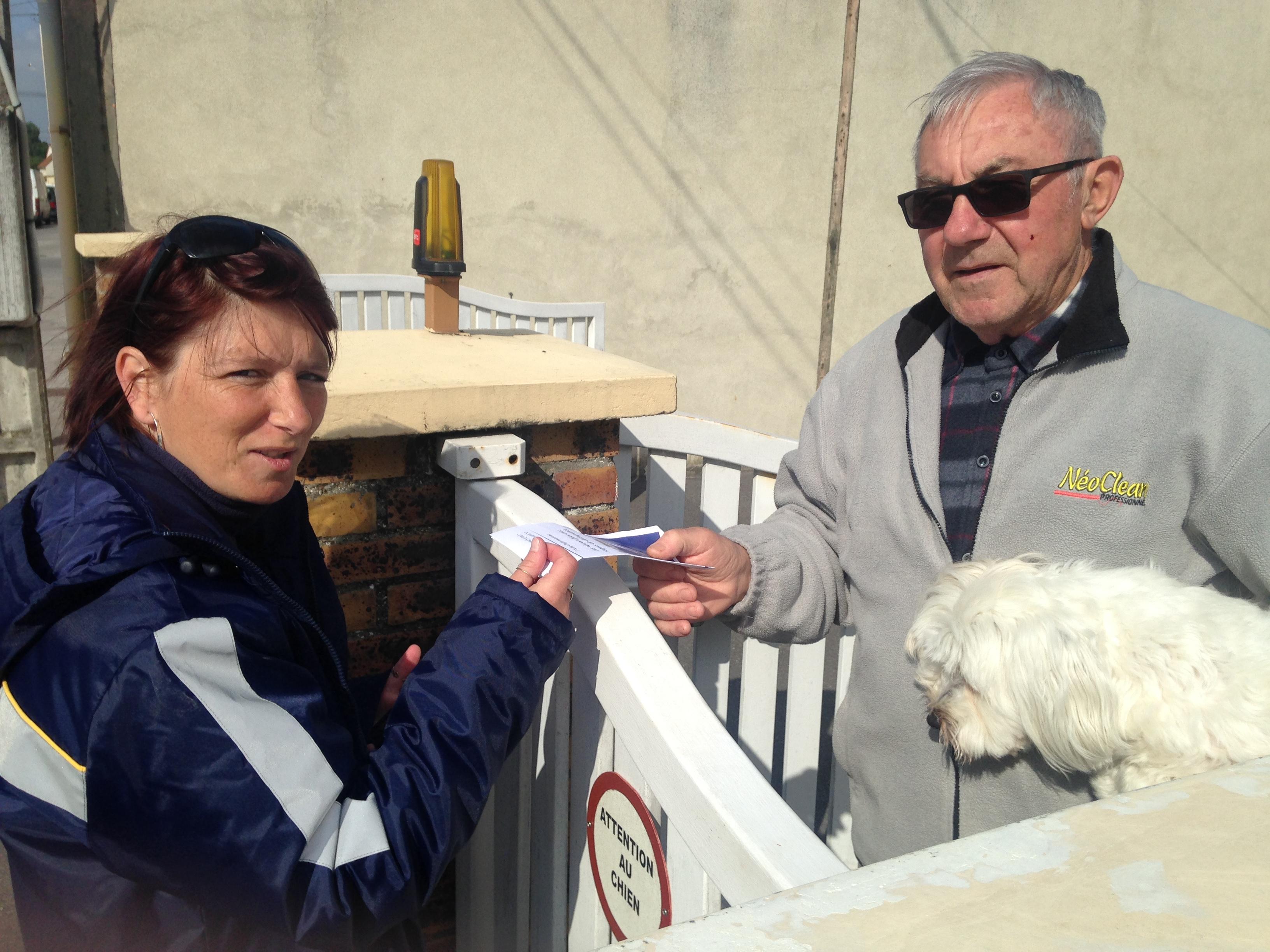 lUne factrice donne à un sénior en main propre un guide pédagogique dans l'Aisne