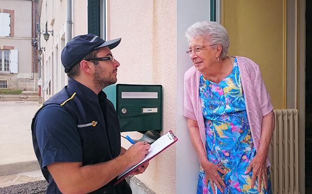 La photo d'une senior répondant au questionnaire que lui soumet un facteur