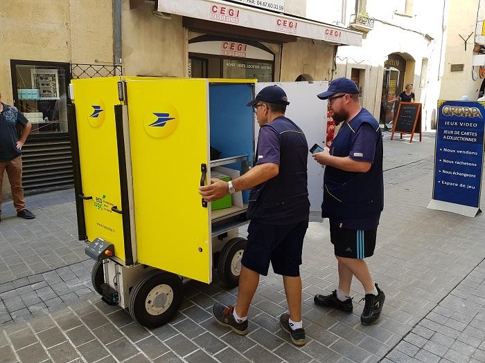 Deux facteurs devant le chariot suiveur : jusqu'à 150 kg de colis.