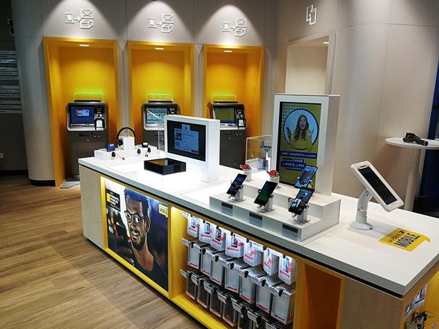 Photo de la première zone de services : un présentoir avec des smartphones au premier plan et des automates au second plan.